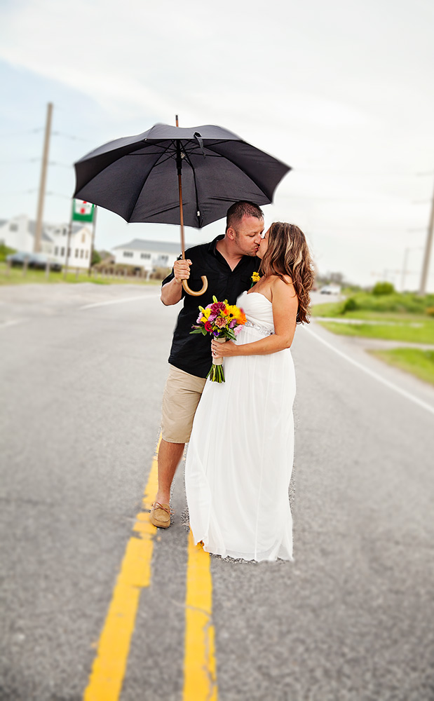 bride and groom with umbrella on beach road in Nags Head NC