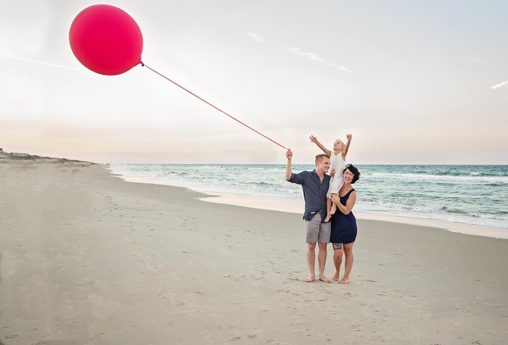 Family of 3 on beach with red balloon in Outer Banks NC