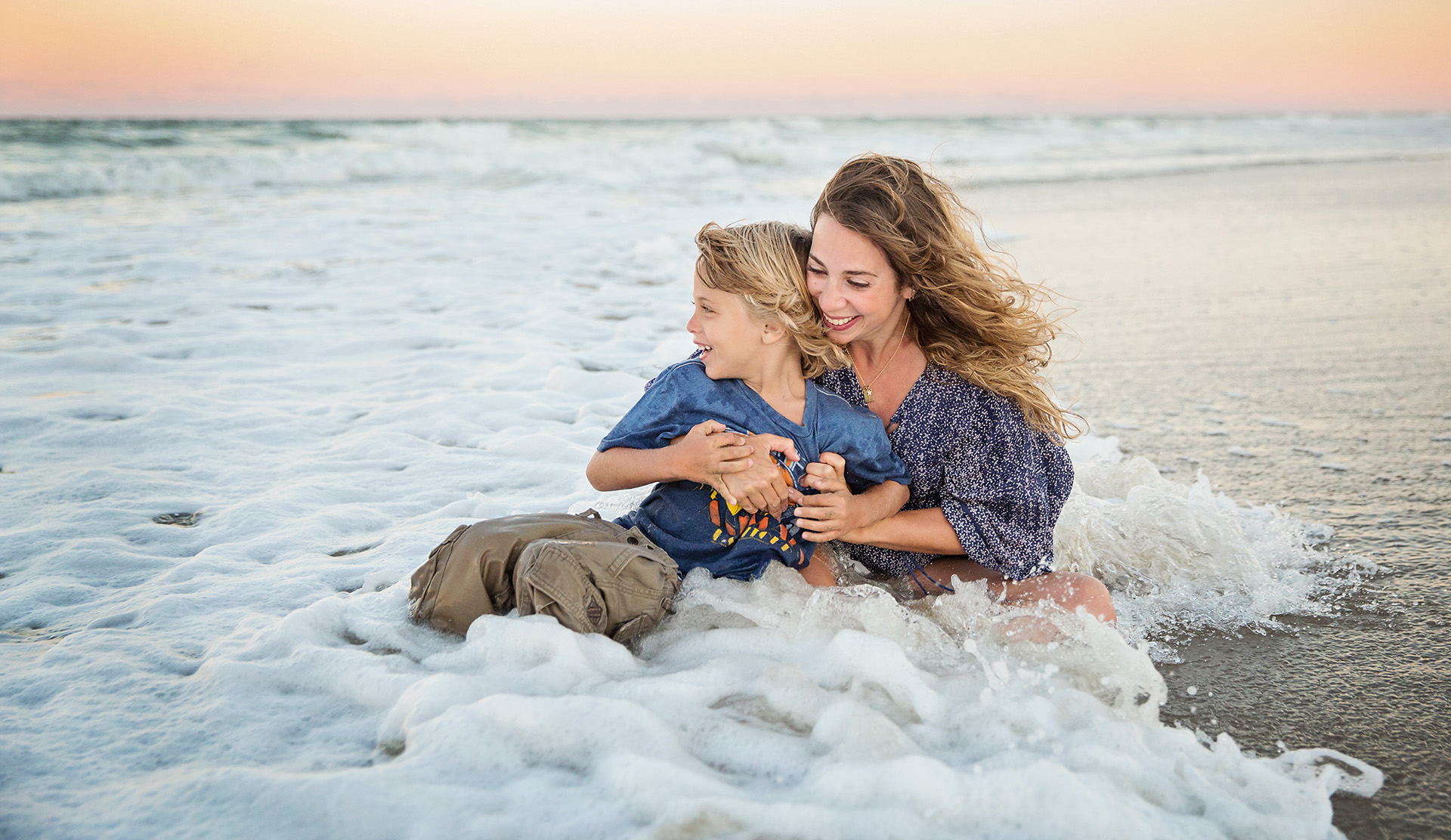 Family photo of Mom and son playing in ocean Corolla NC
