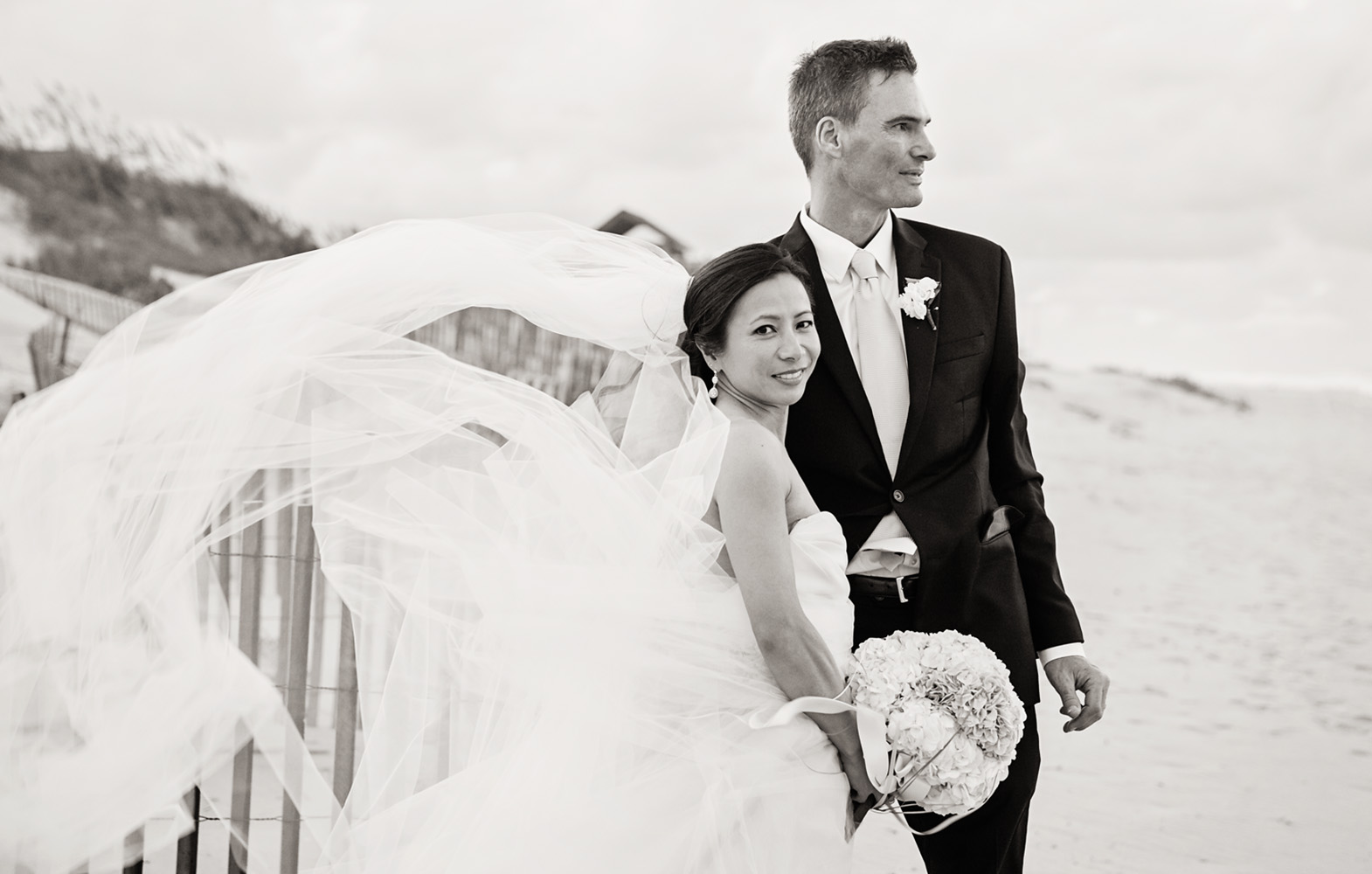 Bride and groom black and white on beach by Jennettes Pier in Nags Head NC