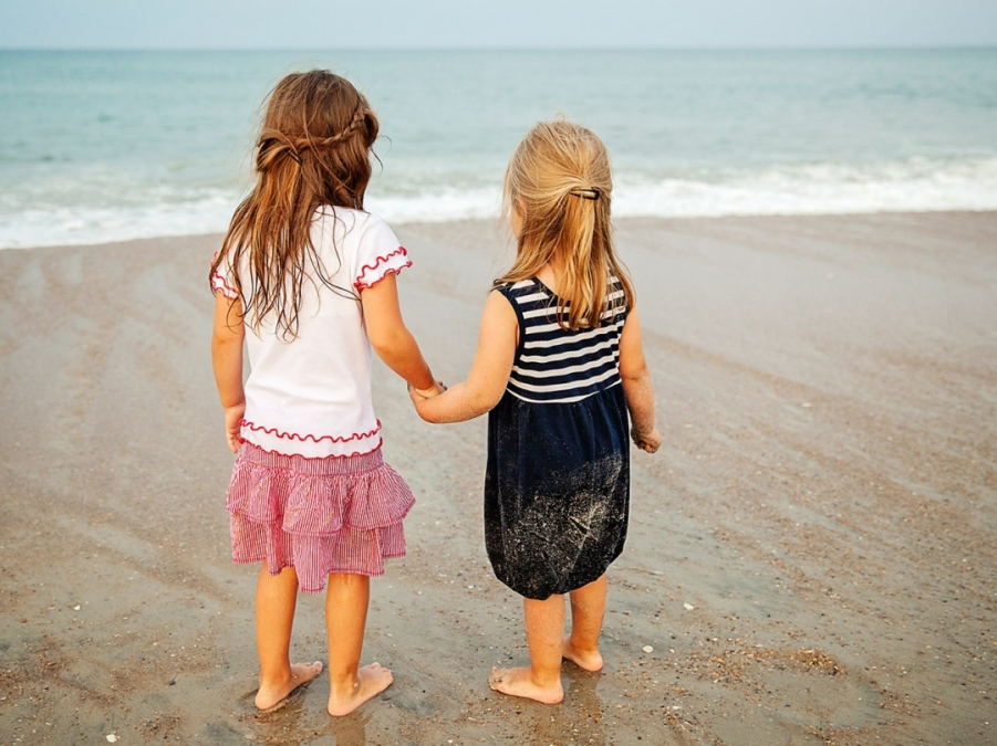 friends hold hands on the beaches of Nags Head NC