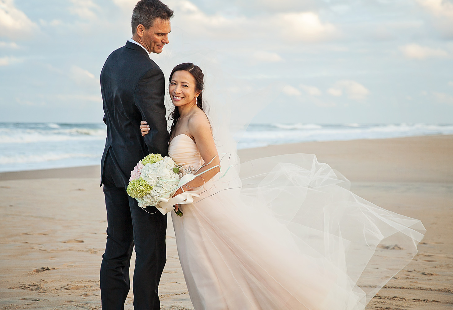 wedding couple on the beach in nags head with amazing dress
