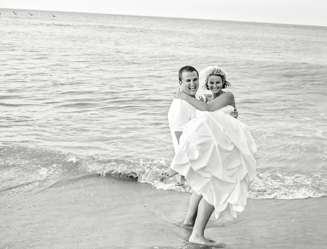 Black and white image of just married couple at the beach
