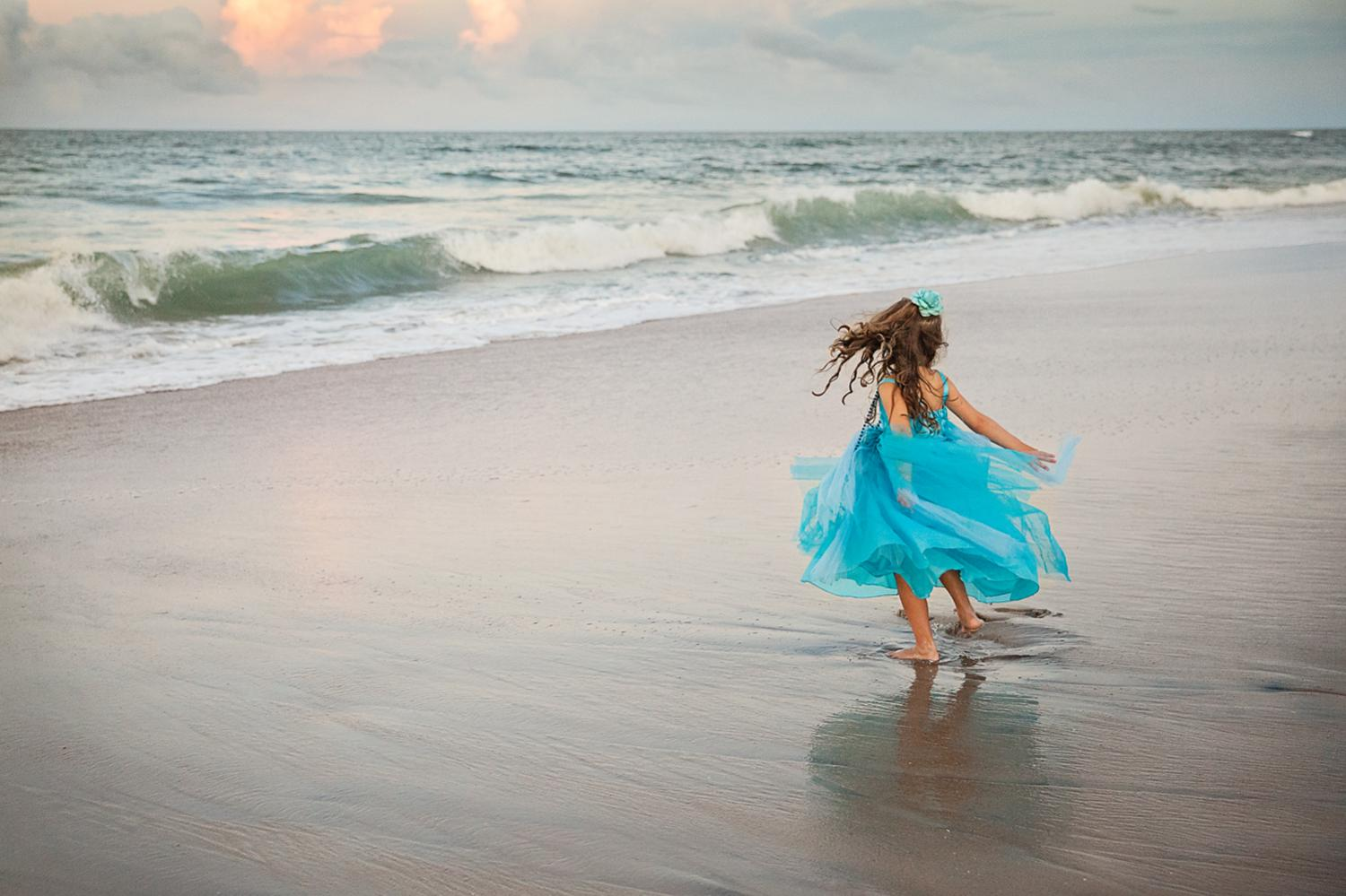 Young girl twirling on the beaches of Nags Head NC