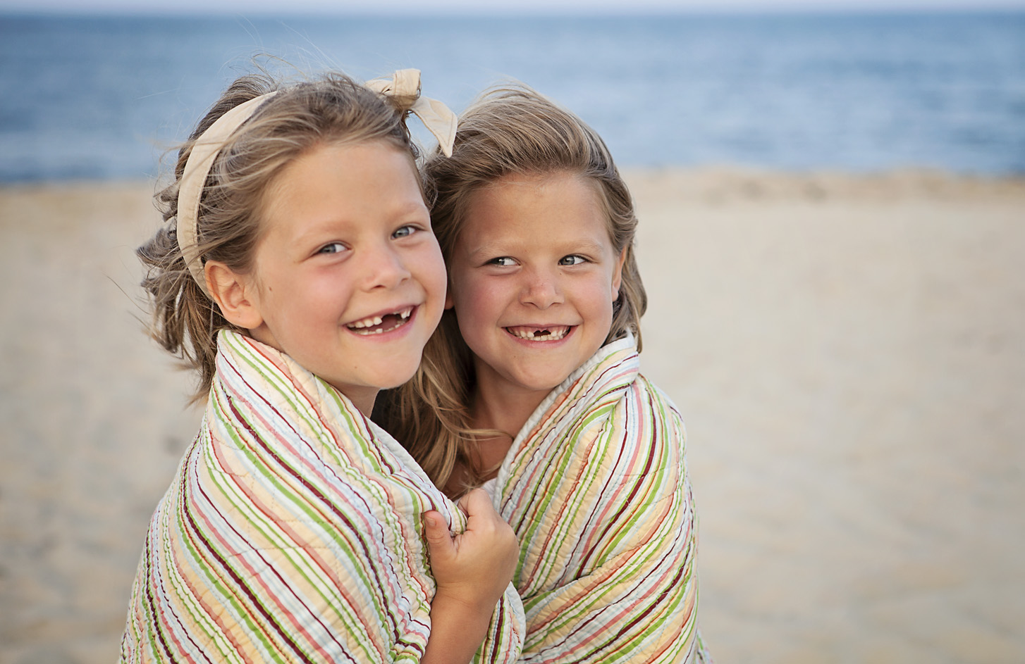 Sisters wrapped in a blanket at the beach in Nags Head NC