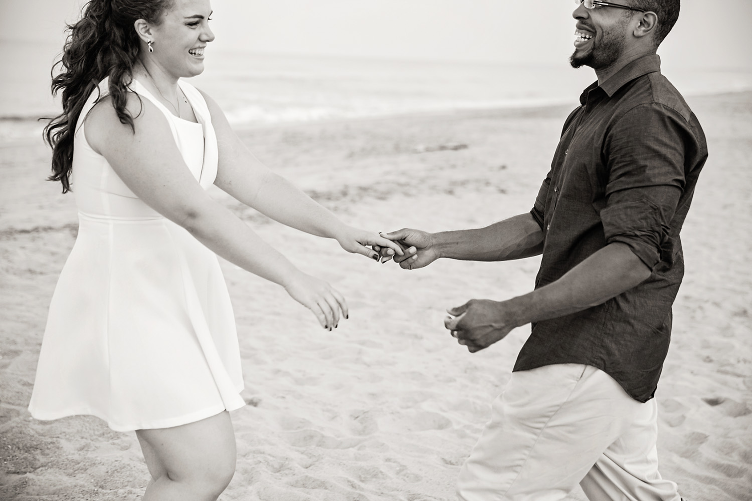 Black and white couple laughing at the beach